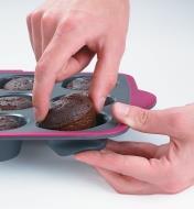 Personne appuyant sous un moule à muffins pour démouler un muffin