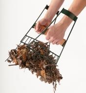 Pair of Large Hand Rakes held in two hands, picking up a pile of leaves