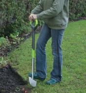 A woman cuts the edge of a garden using the Radius ergonomic edger