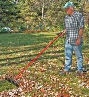 A man uses a Power Rake to rake leaves
