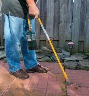 A man uses a Mini Weed Torch to remove weeds from a patio