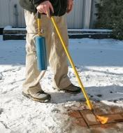 A man melts ice on a walkway using the Mini Weed Torch