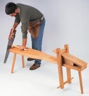 A man uses a shaving horse to saw a dowel