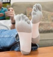 Woman wearing White/Gray Toe Socks with feet resting on coffee table