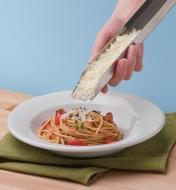 Personne garnissant un bol de pâtes avec du parmesan fraîchement râpé à l'aide un boîtier en acier inoxydable pour râpe
