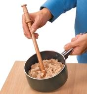 Mixing oatmeal in a pot with a Spurtle