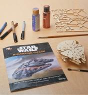 Assembled Millennium Falcon Wooden Model next to the instructions, paints and markers