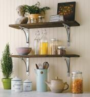 Four concave steel shelf brackets used to mount two shelves in a kitchen