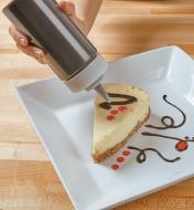 Using a squeeze bottle to add ganache to a cheesecake slice