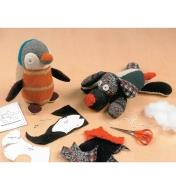 Completed penguin and dog beside pattern and cloth pieces and a pair of scissors