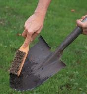 Scraping dirt off a spade using the bevelled end of the Toolshed Brush