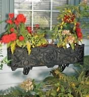 Stratford Planter filled with potted flowers and mounted below a window