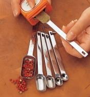 Inserting a measuring spoon into the slender opening of a spice container