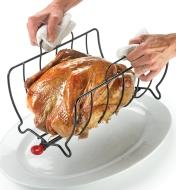 Transferring a roasted chicken to a platter by carrying the rack by its handles