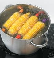 Four cobs of corn with corn holders in a pot of boiling water