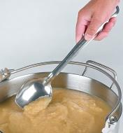 Using the solid slanted spoon to stir apple sauce in a pot