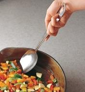 Using the solid slanted spoon to stir diced vegetables in a frying pan