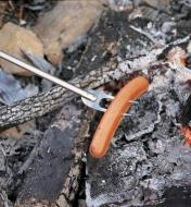 Cooking a hot dog over a fire using the telescoping campfire fork