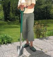 A woman holds the Border Shovel on a patio