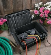 Electrical cords in a garden connected inside a Dribox with the lid off