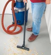Using the floor tool to vacuum up wood shavings