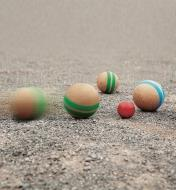 Wooden Pétanque balls rolling on a dirt surface