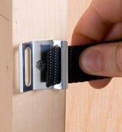 Buckle strap being threaded through wall-mount storage bracket