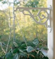 White Victorian Wall Bracket holding a hanging basket on an outdoor post