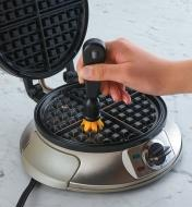 Using the brush with plastic bristles to clean a waffle iron