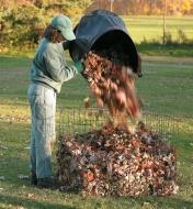 A woman dumps a bin full of leaves into a Wire Compost Bin