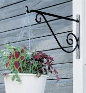Wrought-Iron Wall Bracket holding a hanging basket on an outdoor post