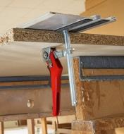A Bessey ratcheting track clamp being used to hold a track-saw guide in position on a panel