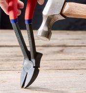 Nail Hunter angled in to wood as a hammer strikes the back