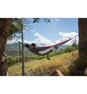 A person lying in a gray/red hammock hammock hung between two trees by a meadow