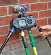 Attaching a hose to one of the electronic water timer's four outlets