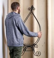 Homme rangeant un support pliant pour plante dans une remise