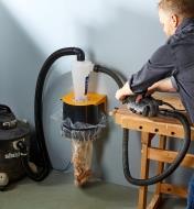A man using Dust Deputy Bagger with a power sander