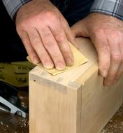 A woodworker uses Mirka Gold sandpaper to sand the dovetailed corner of a wooden box