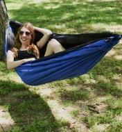 A Kubie multifunction blanket being used as a hammock