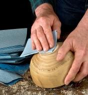 A woodworker sands a turned wooden bowl with a sheet of Norton ProSand 3X Sandpaper