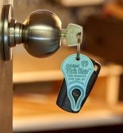 A key inserted in a door lock, with a Tick Key attached to the keychain