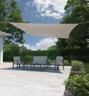 Outdoor patio furniture in the shade of a square shade sail