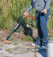 A woman uses the Giant Weed Torch to remove weeds from a walkway