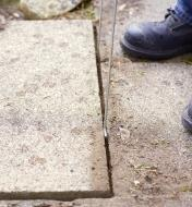 A close view of two SlabSetter tips being slipped between two close-fitting patio stones