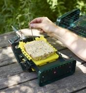 The Squirrel Buster suet feeder being filled with a suet cake