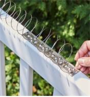 Flexible coil hooked into bracket on railing