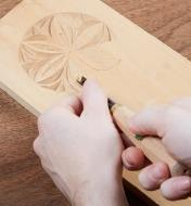 Using a gouge to remove wood in a relief carving