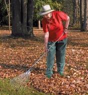 Femme ratissant des feuilles avec un balai à feuilles à manche long
