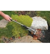Using the Short-Handled Rake to clear fallen leaves between rocks in a garden