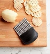 Crinkle Cutter on a cutting board next to potatoes being cut into latticed slices